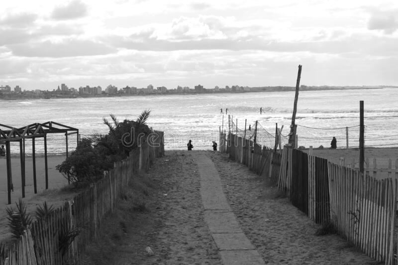 Road To The Sea And The City. Special photo taken in black and white, sandy road, sea plus maritime city, city with coasts, sand and beaches royalty free stock photos