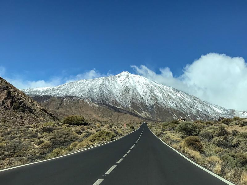 On the road to snowy El Teide. View of El Teide from the road leading there. Snowy El Teide in the background with a straight road toward it stock photography