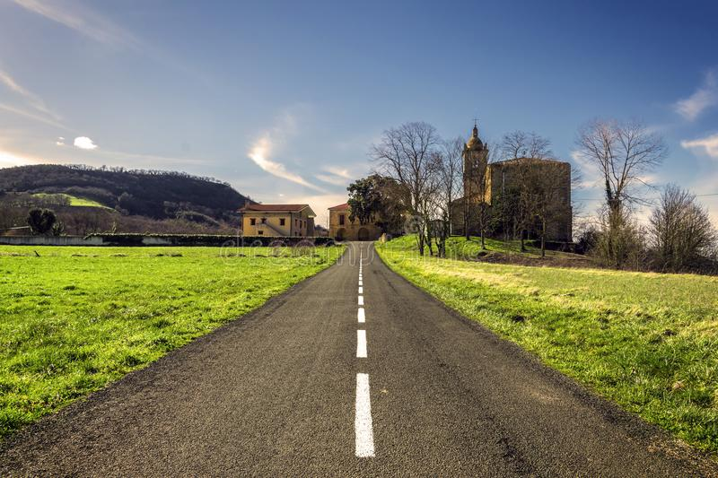 The road to the town. A road that goes towards a town that is in the background. Around there is grass and it is at sunset royalty free stock photography