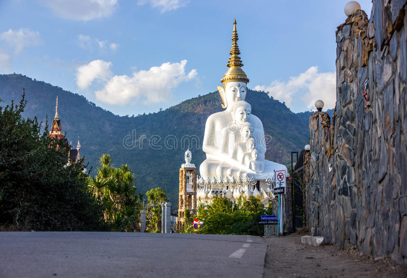 Road to buddha statue. Road to white buddha statue and mountain background with blue sky in afternoon time royalty free stock photography