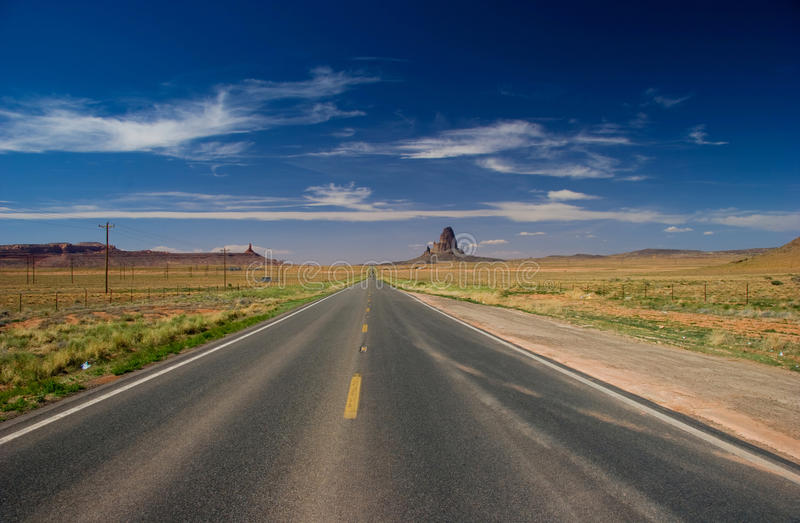 Road towards Monument Valley in the Navajo Nation. Asphalt road heading towards Monument Valley in the Navajo Nation, northeastern Arizona, USA royalty free stock photography