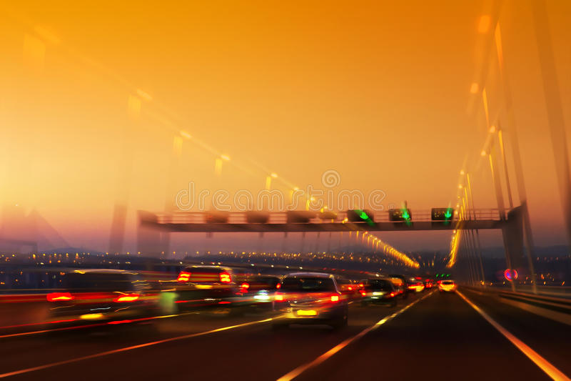 Road Traffic. High traffic road with signs and light trails on sunset stock photography