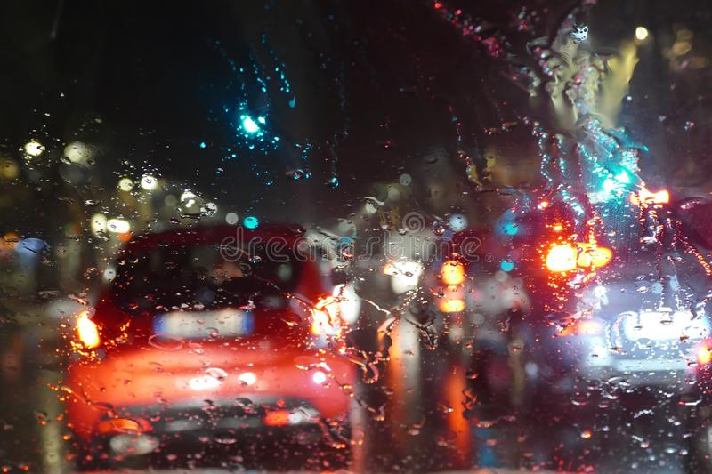 Road traffic in rainy night with cars and lights selective focus on rain drops blur effect. Road traffic in rainy night with cars and lights selective focus on royalty free stock image