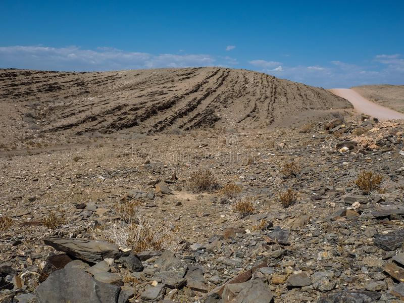Road trip through rock mountain dried dusty landscape background of Namib desert with splitting shale pieces and other stone royalty free stock photos