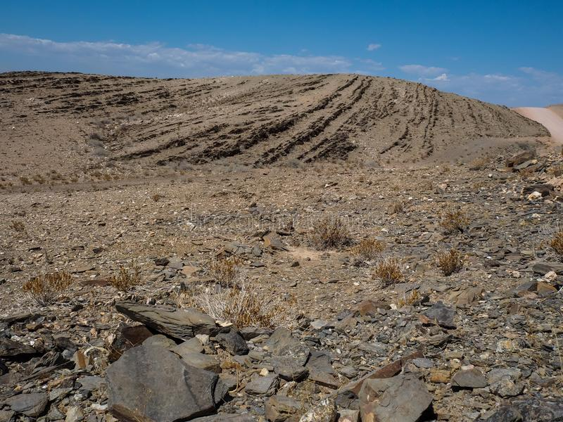 Road trip through rock mountain dried dusty landscape background of Namib desert with splitting shale pieces and other stone. Road trip through rock mountain stock photography