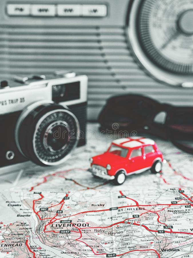 Road trip to Liverpool with red toy car old road map camera radio and sunglasses stock image