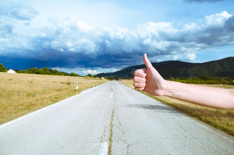 Road trip, travel, gesture and people concept - woman hitchhiking stock photography