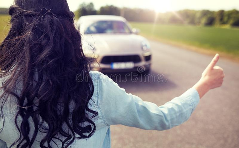 Woman hitchhiking and stopping car with thumbs up stock photos