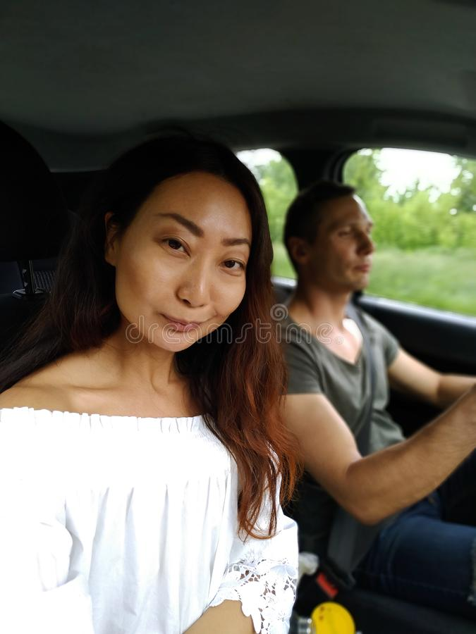 road trip, travel, summer holidays and people concept - happy couple driving in car, girl looking at camera. stock images