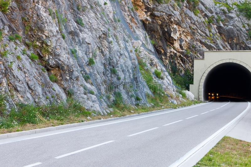Road and tunnel in the mountain. Cars driving out of it with glowing headlights royalty free stock photography