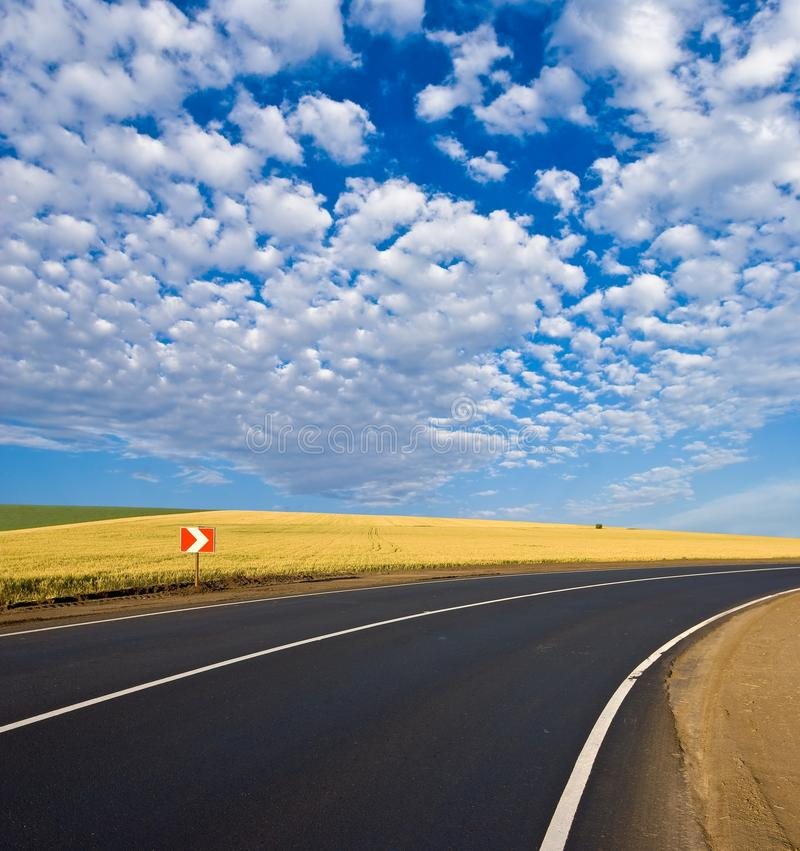 Road turn. Wheat field and blue sky royalty free stock photography