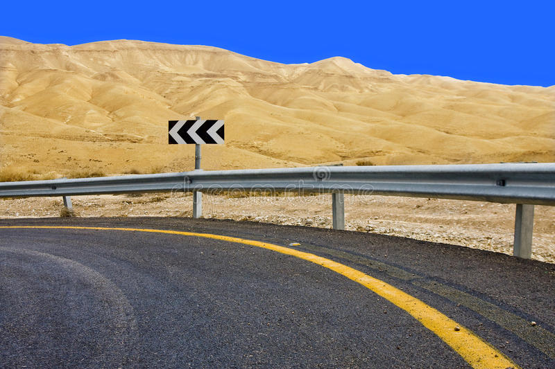 Road turn sign. Sharp curve road turn sign on a desert road stock photos