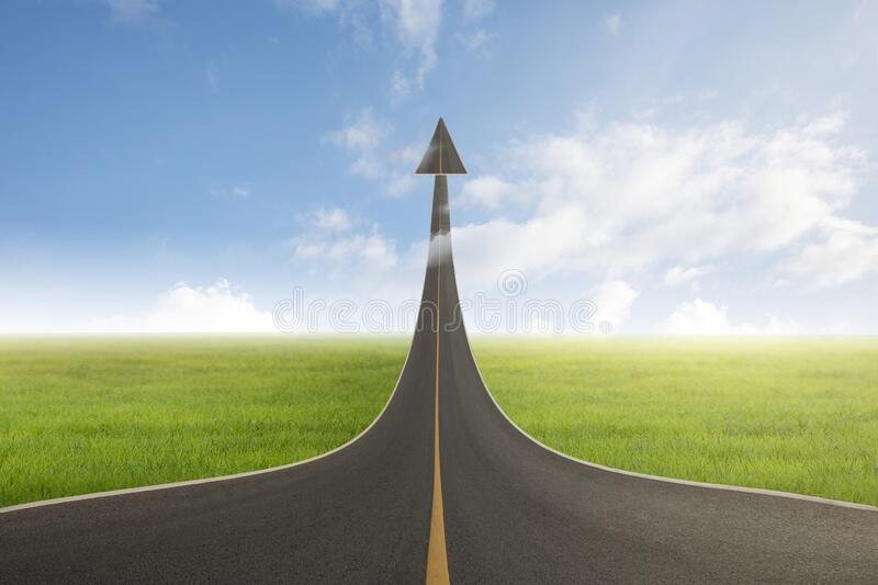 A road turning into an arrow rising upward with success, symbolizing the direction to success royalty free stock photos