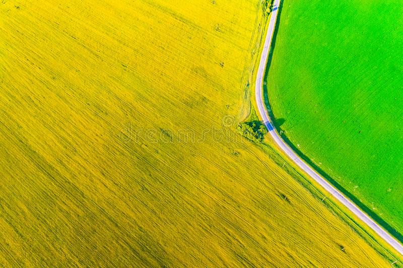 Road turning in farmlands. Aerial landscape. Yellow colza and green cornfield from above. Road turning in farmlands. Aerial landscape. Yellow colza land and royalty free stock photos