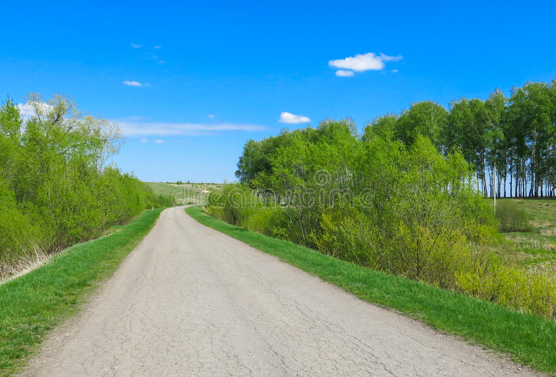 The road turns, summer day. Sunny weather, around trees and hills stock photos