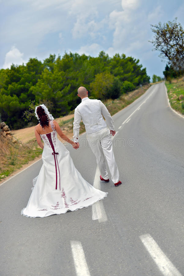 On the road two lives coming together. Bride and groom walking on the road. Two lives become one, two lines on the road become one line. Road to the future royalty free stock photography