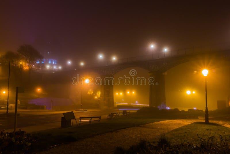 Road under footbridge misty night stock photos