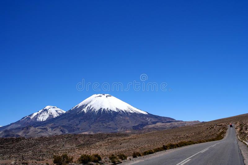Road and Volcanoes in Park Lauca stock image