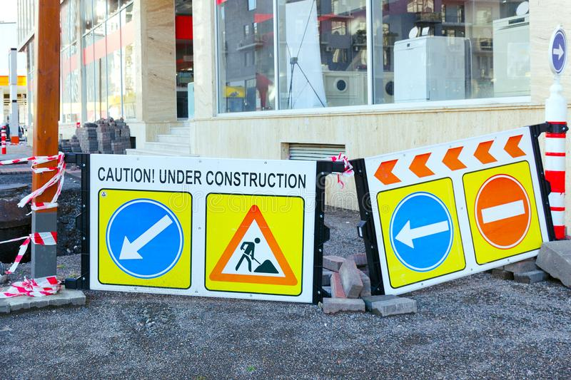 Road warning boards signs with inscriptions caution and under construction. stock images