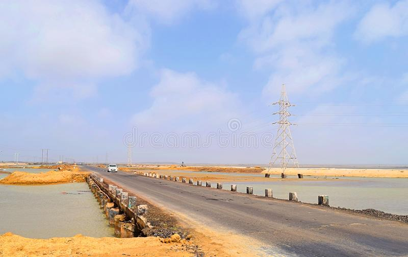 Road with a White Car at Distance and Power Transmission Tower in Flooded Water & Blue Sky - Landschaft in Developing Country stockbild