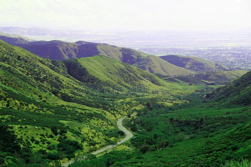 Green, mountain valley with winding road. A road winding through a green mountain side and valley stock photos