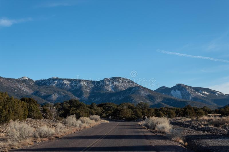 Road in winter desert New Mexico, snowy mountains, American Southwest. Horizontal aspect royalty free stock images