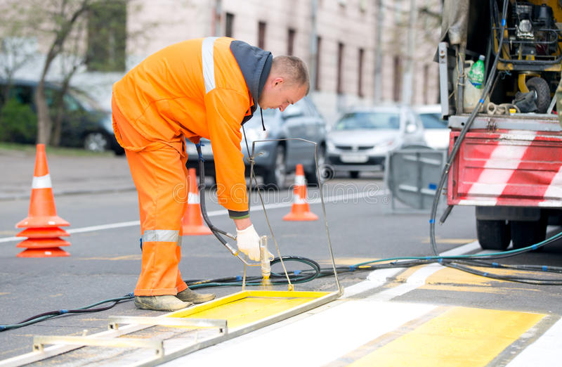 Road worker painting pedestrian crossing line royalty free stock photo