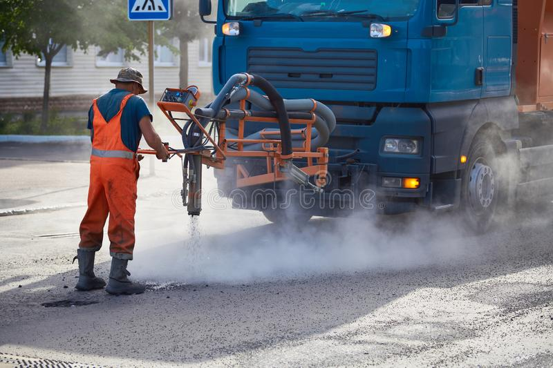 Road worker repairing asphalt coating, using a manipulator. Pitching with hot asphalt injection stock image