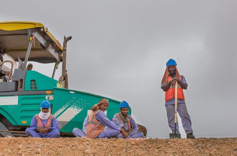 Road workers taking a break. SALALAH, OMAN - CIRCA JULY 2016: Costruction workers taking a break on the side of a road stock photo