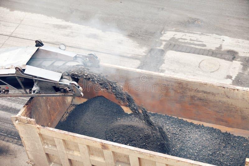 Road works. Asphalt removing machine loading powdered asphalt on the truck royalty free stock images