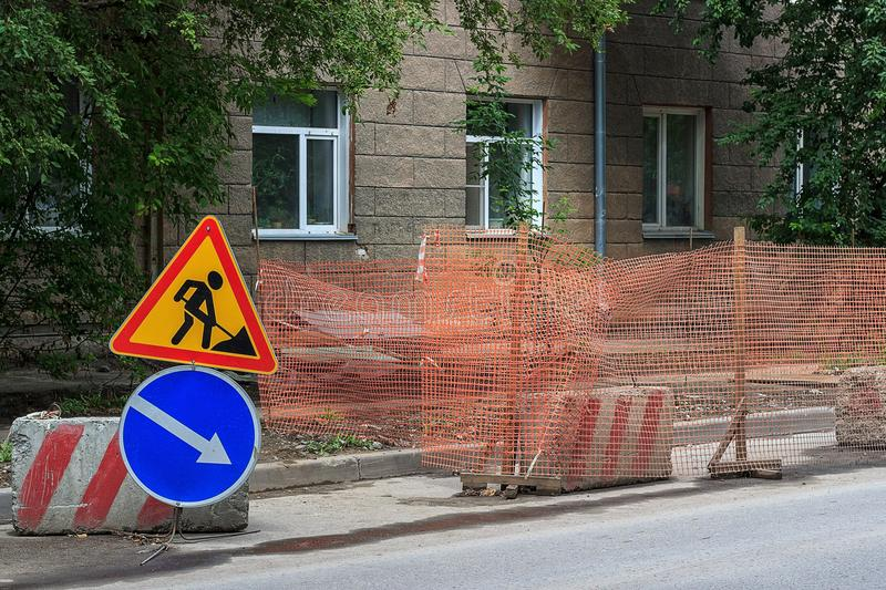 Road works on the city street. Road work and detour signs. Repair work. Road repair in city street. City street construction site with barricades, safety fence stock photos