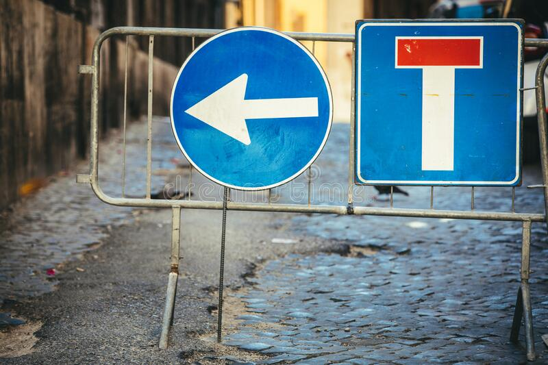 Road works detour road signs. Dead end road and arrow to turn left. Iron crossing barrier. Street with paving cobblestones royalty free stock images