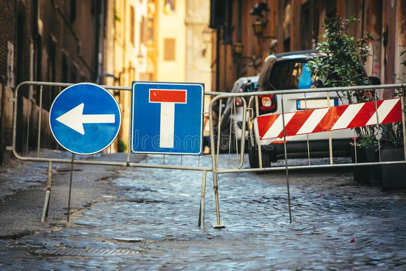 Road works detour road signs. Dead end road and arrow to turn left. Iron crossing barrier. Street with paving cobblestones royalty free stock photography