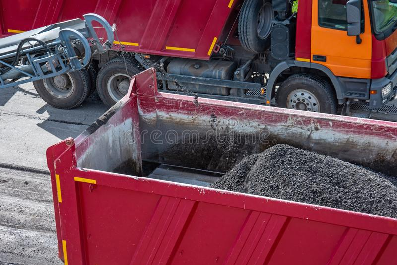 Road works. Dismantling of asphalt pavement. Recycled asphalt crumb is poured over the conveyor belt into the truck body.  stock images