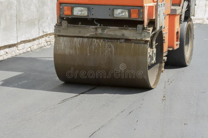 Road works. Laying asphalt. The front part of the asphalt skating rink is depicted. road repair. compaction of the pavement in. Road construction. hard work royalty free stock photos