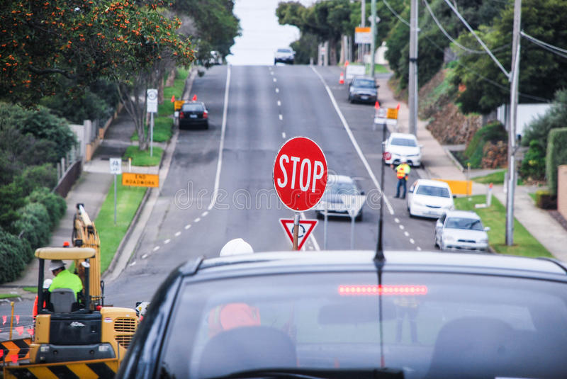 Road works by the roundabout, roadworks crew in action, machinery operating. Victoria, Australia. Stop sign held by the roadworks operator & x28;lollipop man& stock images