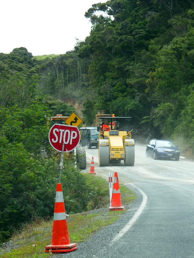 Road works: stop sign, machinery and cars