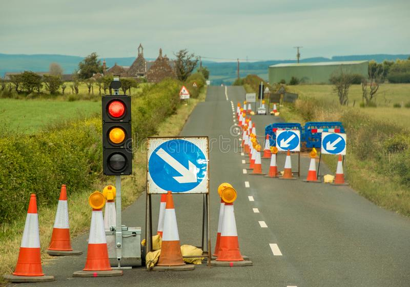 Road Works. Traffic lights and signage on a country road to control around road works stock photo