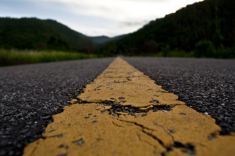 Road with a yellow line. French road with a yellow central line. Hills on the background royalty free stock photography
