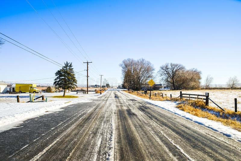 Icy Country Road Around The Farmland In Ellensburg, The Whole Town Is Snowy White Under The Blue Sky, WA, USA. The roads all around Ellensburg are icy and frozen stock photos