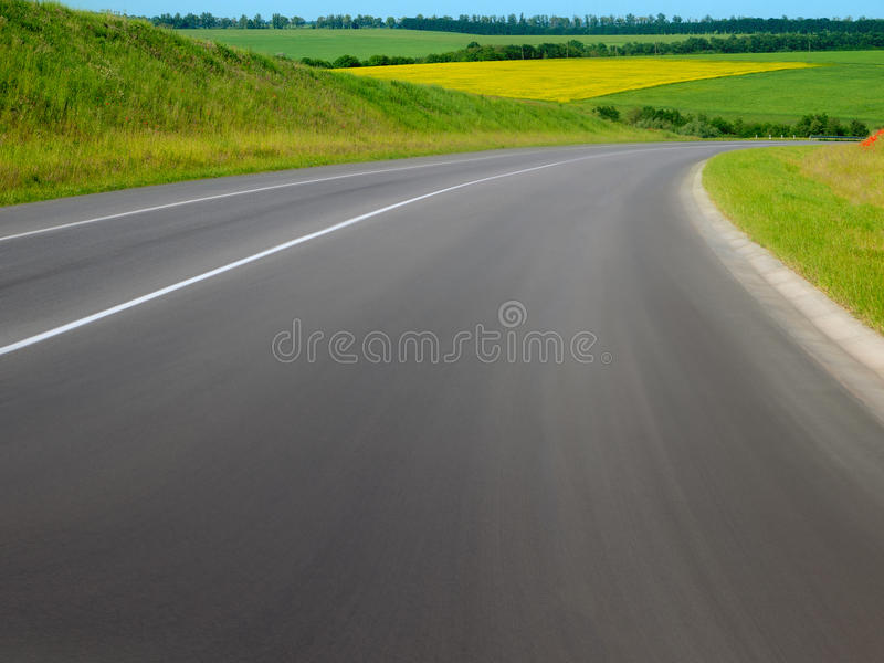 ROADS OF FIELDS. Road passes through the flowering fields royalty free stock photography