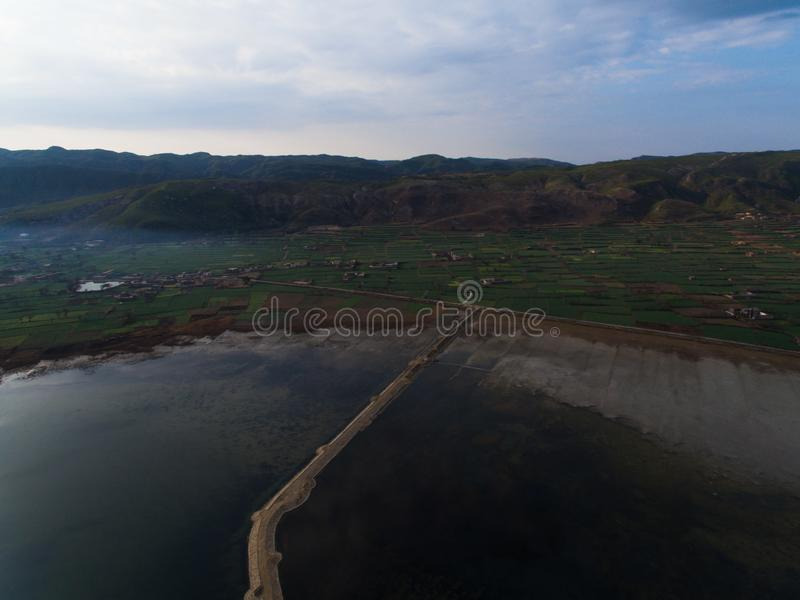Ariel image of a lake with road and fields along its bank royalty free stock photo