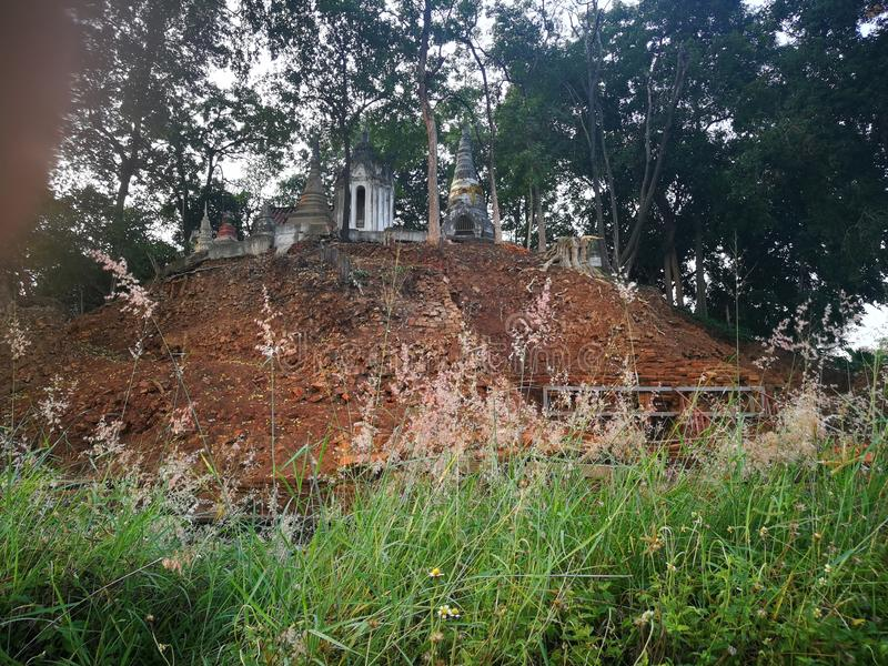Roadside grass  Bricks and ruins of an ancient hilltop covered with trees and religious-related buildings royalty free stock images