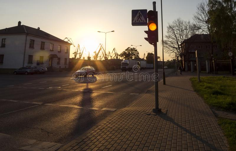 Roadside lanterns and harbor cranes against the backdrop of a sunset in Klaipeda, Lithuania stock photo