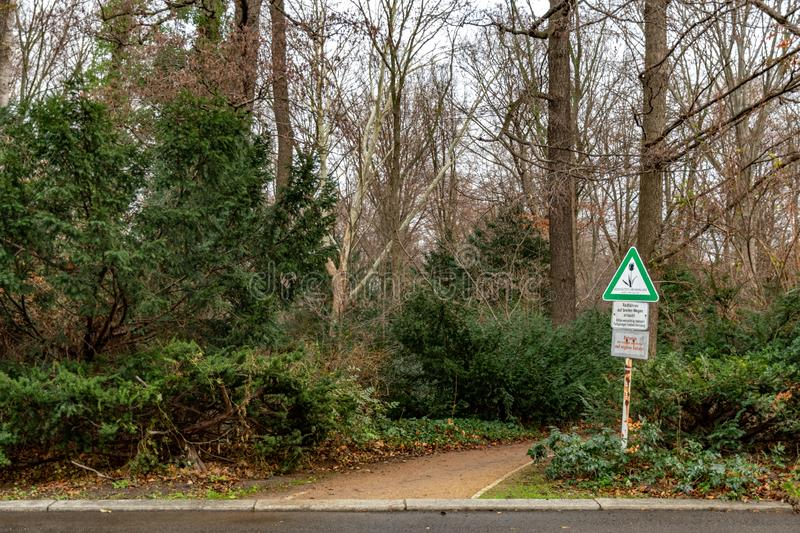 Roadside passes by Tiergarten park of Berlin Germany. Old road sign of triangle shape and nameplates near footpath. Tranquil landscape with nobody in autumn royalty free stock image