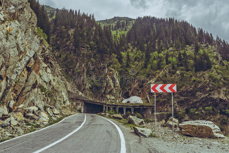 Roadside warning triple chevron sign. Picturesque mountain landscape with roadside triple chevron sign warning for dangerous road turn on sinuous Transfagarasan stock photography