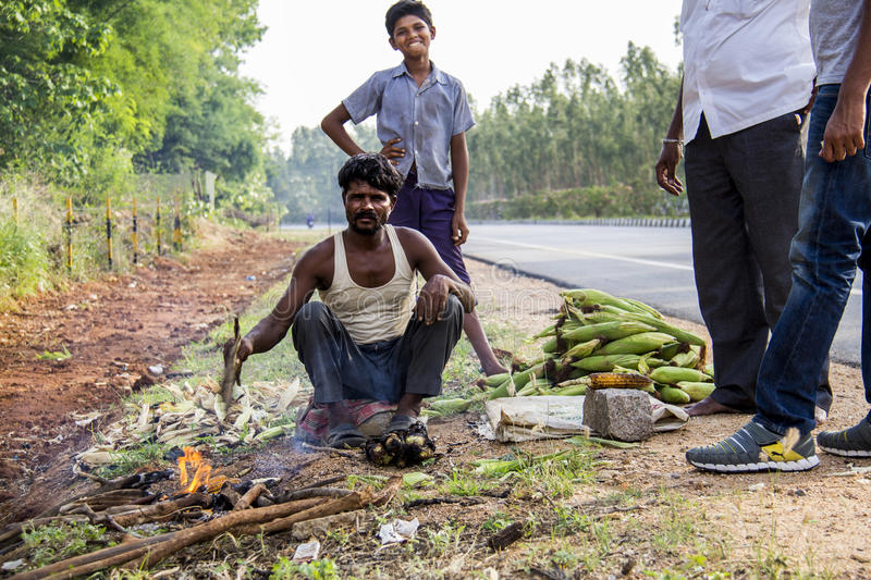 Roadside Worker in South India Roasting Corn. A favorite roadside pit stop for travelers in Southern India, this man is roasting corn on the cob over an open royalty free stock photo
