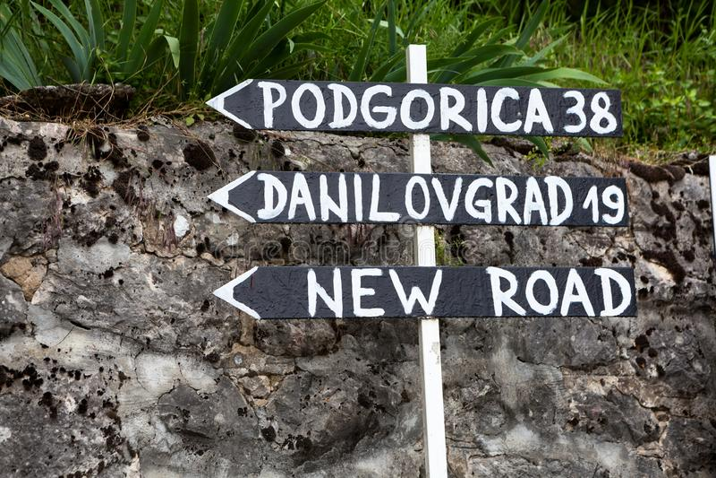 Roadsign με τις κατευθύνσεις σε Podgorica, Danilovgrad και το νέο δρόμο στο μοναστήρι Ostrog Μαυροβούνιο στοκ εικόνες