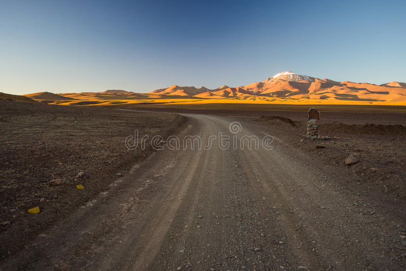 Roadtrip on the Andean highlands, Southern Bolivia. Empty dirt road on high altitude barren mountain range on the highlands of the Andes on the way to the famous royalty free stock images