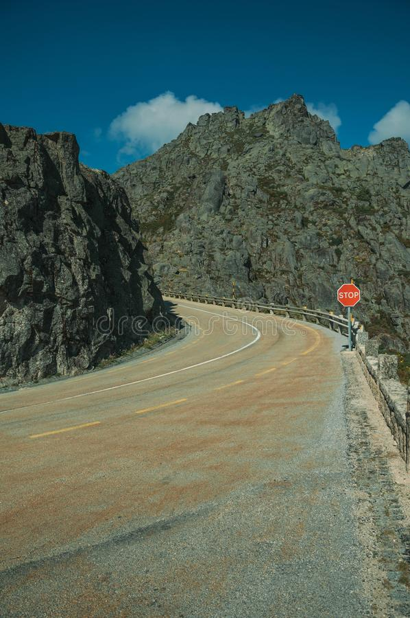 Roadway on rocky landscape with STOP traffic signpost royalty free stock image